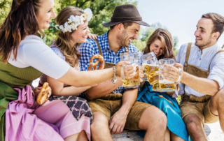 A group of friends cheers with pints of beer at the Fredericksburg Oktoberfest.